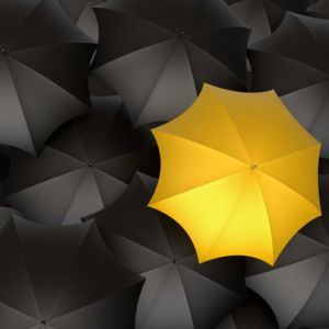 yellow umbrella amongst the black umbrellas